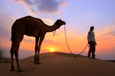 Silhouetted person with a camel at sunset, Thar desert near Jaisalmer, Rajasthan, India photo