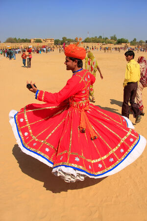 Indian man in traditional dress dancing at Desert Festival, Jaisalmer, Rajasthan, India
