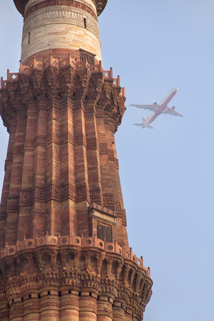 Close up of Qutub Minar tower with airplane in the sky, Qutub Minar complex, Delhi, India photo