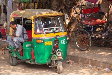 tuktuk: Driver sitting in his tuk-tuk in the street of New Delhi, India