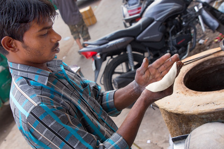 Young man making chapati at streetside restaurant in New Delhi, India