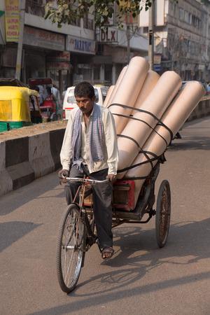 rikscha: Fahrrad-Rikscha, die Waren in der belebten Stra�e von Neu-Delhi, Indien Editorial