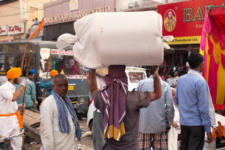 new delhi: Indian man carrying bundle on his head in Chandni Chowk street, New Delhi, India