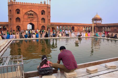 hold up: Indian man with a girl sitting at the pool in Jama Masjid in Delhi, India. The courtyard of the mosque can hold up to twenty-five thousand worshippers