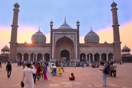 People walking in a courtyard of Jama Masjid at sunset, Delhi, India. The courtyard of the mosque can hold up to twenty-five thousand worshippers