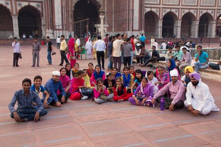 hold up: Group of people sitting at Jama Masjid in Delhi, India. The courtyard of the mosque can hold up to twenty-five thousand worshippers Editorial