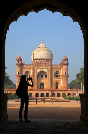 mughal: Tomb of Safdarjung seen from main gateway with silhouetted person taking photo, New Delhi, India. It was built in 1754 in the late Mughal Empire style. Editorial