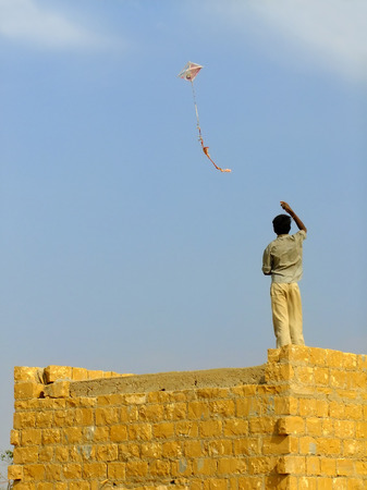 flying man: Indian boy flying kite from the roof of traditional house in Thar desert near Jaisalmer, Rajasthan, India. Thar desert forms a natural boundary between India and Pakistan Stock Photo