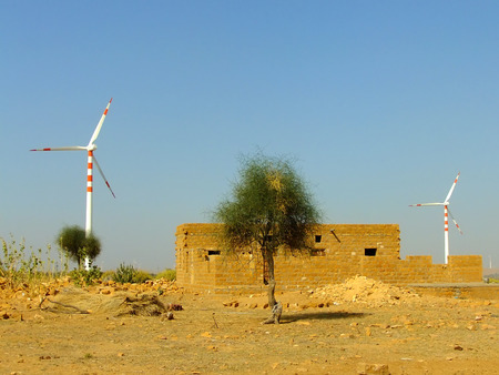 jaisalmer: Small village with traditional houses and windmills in Thar desert near Jaisalmer, Rajasthan, India. Thar desert forms a natural boundary between India and Pakistan Stock Photo