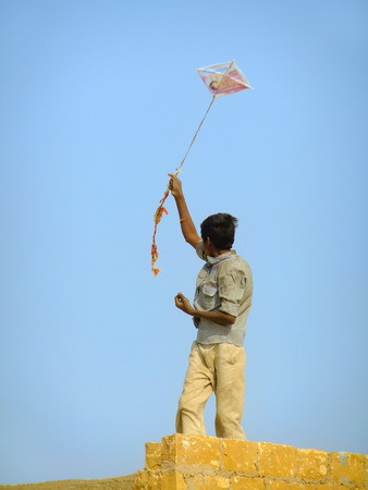 thar: Indian boy flying kite from the roof of traditional house in Thar desert near Jaisalmer, Rajasthan, India. Thar desert forms a natural boundary between India and Pakistan Stock Photo