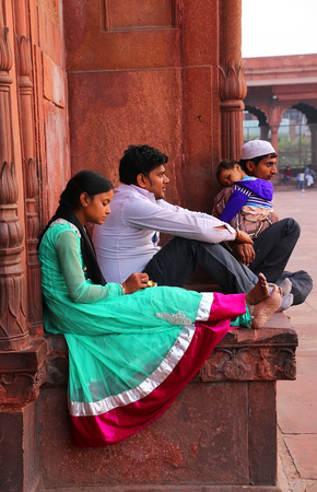 sacra famiglia: Indian woman and men sitting at Jama Masjid in Delhi, India. The courtyard of the mosque can hold up to twenty-five thousand worshippers