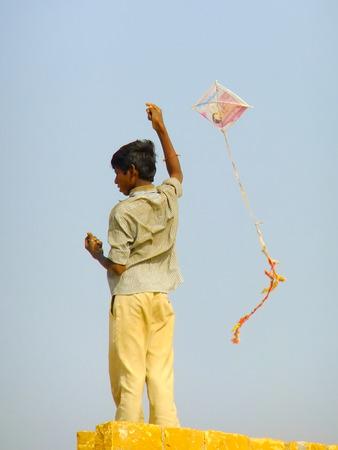 hobby hut: Indian boy flying kite from the roof of traditional house in Thar desert near Jaisalmer, Rajasthan, India. Thar desert forms a natural boundary between India and Pakistan Editorial