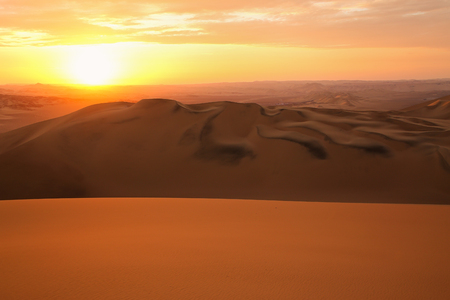 silhoutted: Sand dunes near Huacachina at sunset in Ica region, Peru.