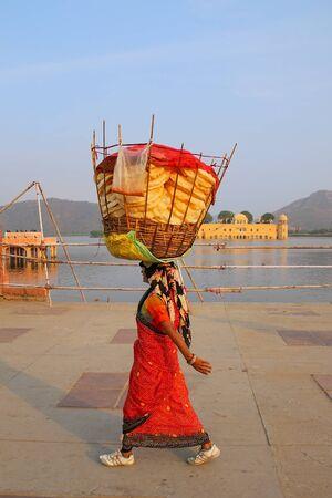 sagar: Indian woman with basket on her head walking by Man Sagar Lake in Jaipur, Rajasthan, India.