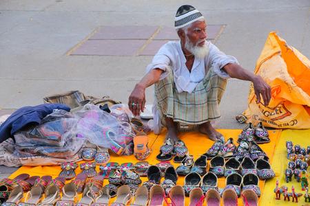 sagar: Local man selling slippers at the market by Man Sagar Lake in Jaipur, Rajasthan, India.