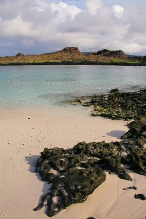 chinese hat: Santiago island seen from the beach of  Chinese Hat island in Galapagos National Park, Ecuador.
