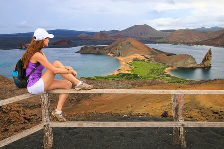 bartolome: Young woman enjoying the view of Pinnacle Rock on Bartolome island, Galapagos National Park, Ecuador. This island offers some of the most beautiful landscapes in the archipelago.