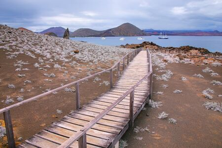 bartolome: Wooden boardwalk on Bartolome island in Galapagos National Park, Ecuador. The island consists of an extinct volcano and a variety of red, orange, green, and glistening black volcanic formations. Stock Photo