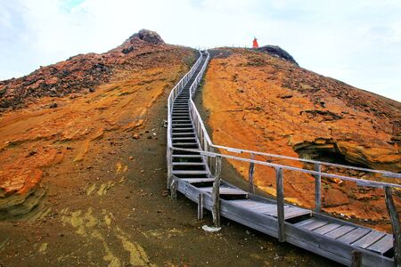 bartolome: Wooden boardwalk leading to the viewpont on Bartolome island in Galapagos National Park, Ecuador. The island consists of an extinct volcano and a variety of red, orange, green, and glistening black volcanic formations.