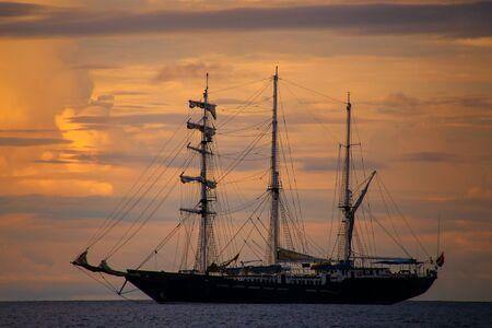 bartolome: Silhouette of a sailboat at sunset near Bartolome island in Galapagos National Park, Ecuador.