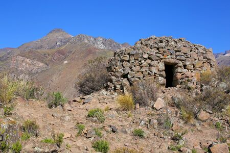 food storage: Pre-Incan round house named colca near Chivay in Peru. Colcas are circular stone structures used for food storage or burials. Stock Photo