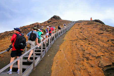 bartolome: Group of tourists walking on a boardwalk on Bartolome island, Galapagos National Park, Ecuador. The island consists of an extinct volcano and a variety of red, orange, green, and glistening black volcanic formations.