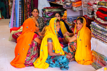 Local women sitting in a store at Johari Bazaar street in Jaipur, Rajasthan, India. Jaipur is the capital and the largest city of Rajasthan.