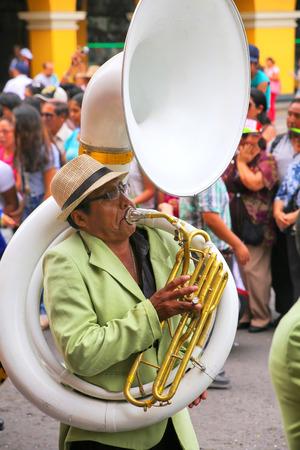 Hombre local jugando sousaphone durante el Festival de la Virgen de la Candelaria en Lima, Perú. El núcleo de la fiesta es el baile y la música interpretada por diferentes escuelas de danza.