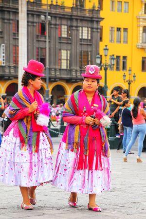 Mujeres locales caminando en la Plaza Mayor durante el Festival de la Virgen de la Candelaria en Lima, Perú. El núcleo del festival es el baile y la música interpretada por diferentes escuelas de baile. Editorial