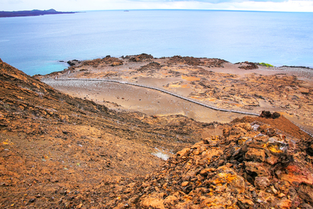 bartolome: View of Bartolome island in Galapagos National Park, Ecuador. The island consists of an extinct volcano and a variety of red, orange, green, and glistening black volcanic formations. Stock Photo