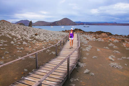bartolome: Young woman walking on a boardwalk on Bartolome island, Galapagos National Park, Ecuador. The island consists of an extinct volcano and a variety of red, orange, green, and glistening black volcanic formations.