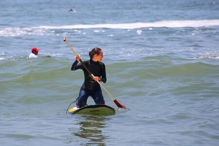 Young woman paddling on a board in Punta Hermosa, Peru. Punta Hermosa is a popular beach town not far from Lima. Stock Photo