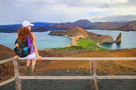 Jonge vrouw genieten van het uitzicht op Pinnacle Rock on Bartolome eiland, Galapagos National Park, Ecuador. Dit eiland biedt enkele van de mooiste landschappen van de archipel.