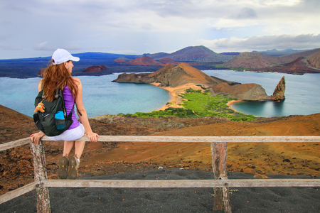 Young woman enjoying the view of Pinnacle Rock on Bartolome island, Galapagos National Park, Ecuador. This island offers some of the most beautiful landscapes in the archipelago.