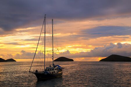 chinese hat: Silhouetted tourist sailboat at sunrise anchored near Chinese Hat island in Galapagos National Park, Ecuador Stock Photo
