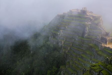 voted: Agricultural stone terraces with fog at  Machu Picchu, Peru. In 2007 Machu Picchu was voted one of the New Seven Wonders of the World.