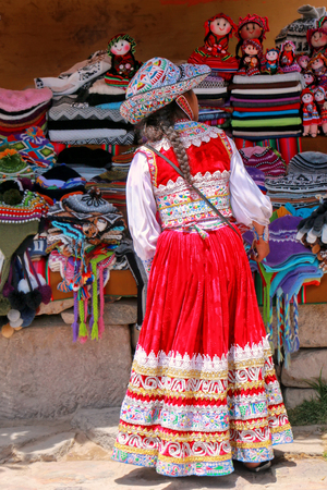 maca: Girl in traditional dress standing at the market in Maca village in Colca Canyon, Peru. Maca is one of the three main tourist towns of the Colca Canyon.