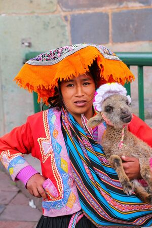 typical: Local woman in traditional dress holding lamb in the street of Cusco, Peru. In 1983 Cusco was declared a World Heritage Site by UNESCO