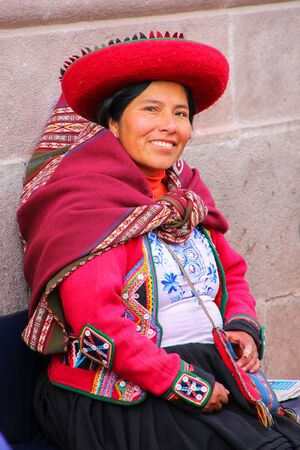 Local woman in traditional dress sitting in the street of Cusco, Peru. In 1983 Cusco was declared a World Heritage Site by UNESCO