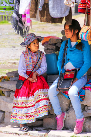 maca: Local girls sitting at the market in Maca village in Colca Canyon, Peru. Maca is one of the three main tourist towns of the Colca Canyon. Editorial