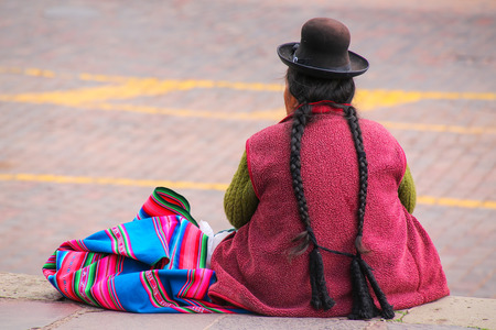 Local woman sitting at Plaza de Armas in Cusco, Peru. In 1983 Cusco was declared a World Heritage Site by UNESCO