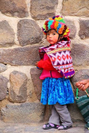 Local girl standing near Inca Fortress in Ollantaytambo, Peru. Ollantaytambo was the royal estate of Emperor Pachacuti who conquered the region. Editorial