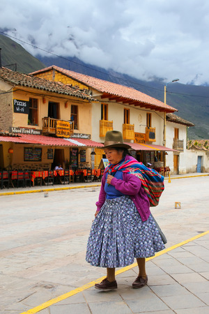 typical: Local woman walking in the street of Ollantaytambo, Peru. Ollantaytambo was the royal estate of Emperor Pachacuti who conquered the region.
