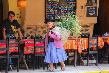 typical: Local woman walking with keperina full of grass in the street of Ollantaytambo, Peru. Ollantaytambo was the royal estate of Emperor Pachacuti who conquered the region.