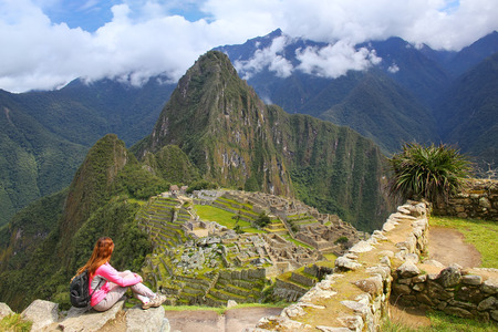 Woman enjoying the view of Machu Picchu citadel in Peru. In 2007 Machu Picchu was voted one of the New Seven Wonders of the World. Imagens