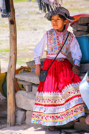 maca: Girl in traditional dress sitting at the market in Maca village in Colca Canyon, Peru. Maca is one of the three main tourist towns of the Colca Canyon.