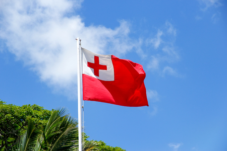 sovereign: National flag of Tonga against blue sky. Tonga is a Polynesian sovereign state and archipelago. Stock Photo