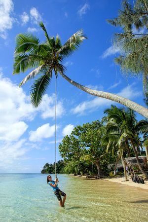 Young woman swinging on a rope swing at Pangaimotu island near Tongatapu island in Tonga. Kindom of Tonga is an archipelago comprised of 169 islands