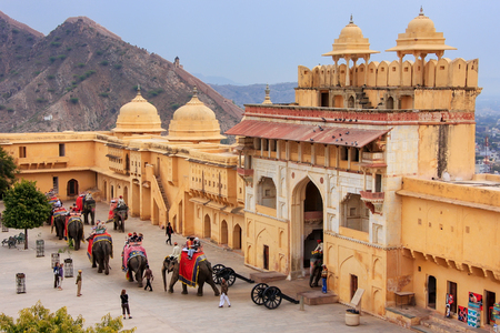 Decorated elephants entering Suraj Pol in Jaleb Chowk (main courtyard) in Amber Fort, Rajasthan, India. Elephant rides are popular tourist attraction in Amber Fort.