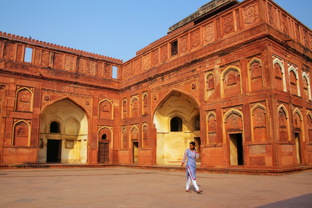 uttar pradesh: Woman walking in the courtyard of Jahangiri Mahal in Agra Fort, Uttar Pradesh, India. The fort was built primarily as a military structure, but was later upgraded to a palace.